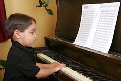 Young boy playing piano Stock Photos
