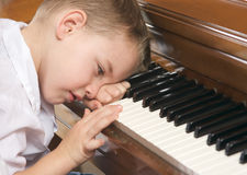 Young Boy Playing the Piano. Young Boy with Head on Hand Playing the Piano Royalty Free Stock Images