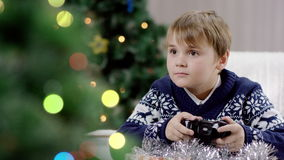 Young boy playing playstation. Young boy opening Christmas presents. boy playing playstation stock video footage