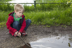 Young boy playing at a puddle Stock Photography