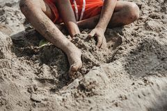 Young boy playing with sand at the beach Stock Photos