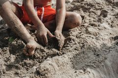 Young boy playing with sand at the beach Stock Image