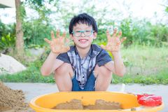 Young boy playing sand in sandbox Stock Image
