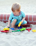 Young boy playing in the sandbox Stock Image