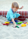 Young boy playing in the sandbox Stock Images