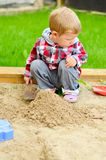 Young boy playing in the sandbox Stock Photo