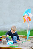 Young boy playing in the sandbox Stock Photos