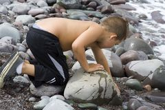 Young Boy playing by the sea. (digging in the gravel Stock Images