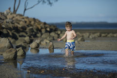 Young boy playing in shallow water Royalty Free Stock Photos