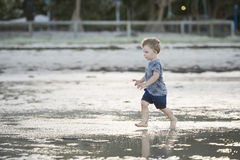 Young boy playing in shallow water Stock Images