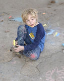 Young boy playing with sidewalk chalk Stock Images