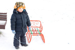 Young boy playing with a sled in snow. Standing holding the rope in his hand as he waits for someone to give him a helping hand Royalty Free Stock Image
