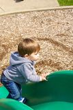 Young boy playing on slide Royalty Free Stock Photos