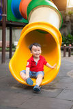 Young Boy Playing On Slide In Playground Stock Image