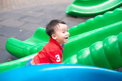 Young Boy Playing On Slide In Playground Stock Photos