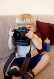 Young boy playing with SLR digital camera royalty free stock image