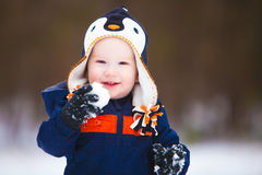 Young Boy Playing in Snow 2. A young boy holding a snow ball and wearing a winter coat and hat smiles as he looks the camera Royalty Free Stock Images