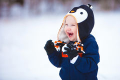Young Boy Playing in Snow. A young boy wearing a winter coat and hat laughs as he plays in the snow Stock Photo