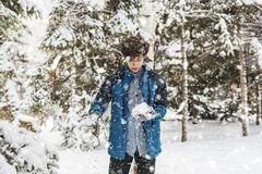 Young boy playing snowball and other winter activities on a snowy day in the park f stock photo