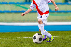 Young Boy Playing Soccer Football Match. Young boys playing football soccer game. Running players in blue and white uniforms Stock Photography