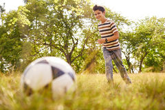 Young boy playing soccer game hitting ball Royalty Free Stock Photography