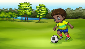 A young boy playing soccer near the river Stock Image
