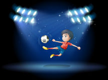 A young boy playing soccer with spotlights Stock Image