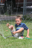YOung boy playing in the sprinkler Royalty Free Stock Image
