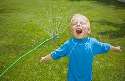 Young boy playing in the sprinklers outdoors royalty free stock image