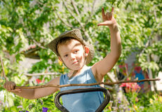 Young boy playing with a stick and gesturing Stock Photo