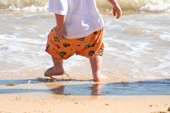 Young boy playing in surf. A closeup view of the feet and legs of a little preschool boy as he plays on the beach in the surf and waves of the ocean stock photo