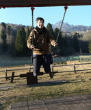 Young boy playing on a swing in a playground in the mountains Royalty Free Stock Image