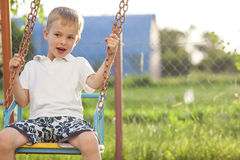 Young boy playing on swings in sunny summer day Stock Photos