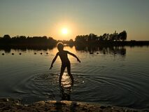 Child throwing a rock into a lake