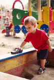 Young Boy Playing with Toy Car in Sandbox Stock Image