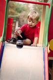 Young Boy Playing with Toy Car on Slide Royalty Free Stock Images