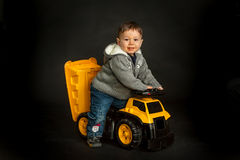 Young boy playing on toy dump truck Royalty Free Stock Photos