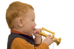 Young boy playing toy trumpet. On isolated white background Stock Images