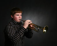Young boy playing trumpet Stock Photos