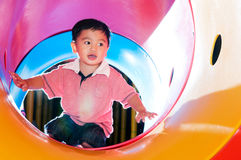 Young Boy Playing In Tube Slide Stock Images