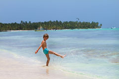 Young boy playing in the turqoise water on a beach. Young boy playing in the turqoise water of a Caribbean island royalty free stock image