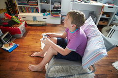 Young Boy Playing Video Game In Bedroom Stock Photography