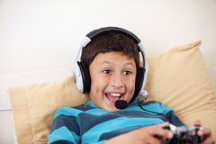 Young boy playing video game with his friends. With headset and microphone with copy space Stock Image