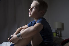 A Young Boy Playing Video Games. A young boy watching the tv while playing video games Stock Photos