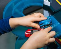 Young boy playing with vintage toy cars at home. Selective focus on hand of boy and toy.  Stock Photography