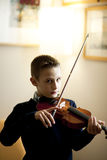 Young boy playing violin Stock Images