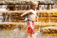 Young boy playing in water fountain. Little boy in red swimtrucks splashing in water fountain Stock Images