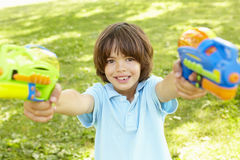 Young Boy Playing With Water Pistols In Park Stock Photos