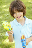 Young Boy Playing With Water Pistols In Park Stock Image