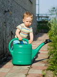 Young boy playing with the watering can Royalty Free Stock Images